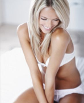 A blonde woman in white lingerie sitting on a bed.